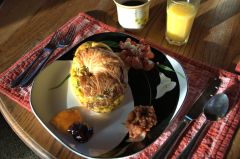 Baked egg croissant with fresh tomatoes and feta, salsa, and jams.
