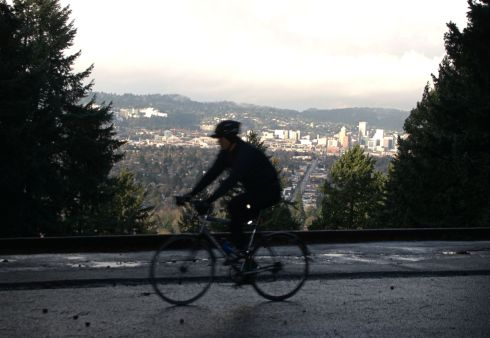 A cyclist rides in the shade while a morning sunbeam lights up Portland in the Willamette valley.