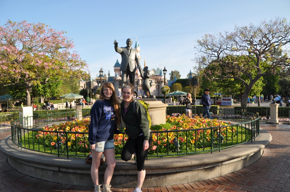 Tara and I stand with Mickey and Walt, in front of the iconic Disney castle.