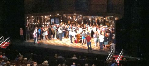 Pre-show performance of Once, with audience members onstage enjoying live music from the actors.