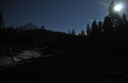 Moon sparkles across the mountain and makes the river glow.