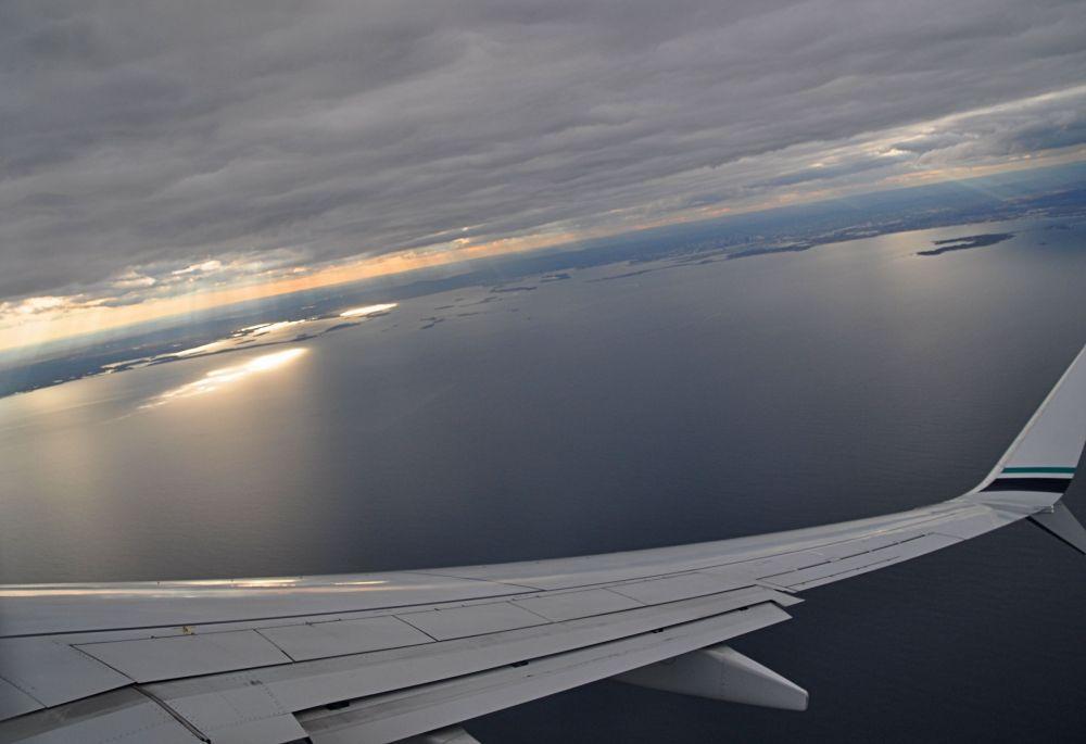 Plane banks as we head toward the Boston bay. Crepuscular rays light up the shoreline like an invitation.
