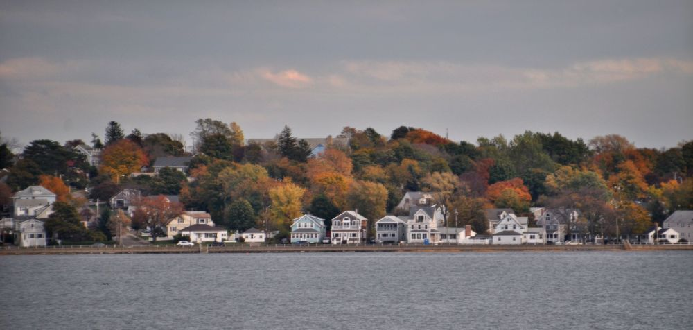 New England homes and foliage across the bay.