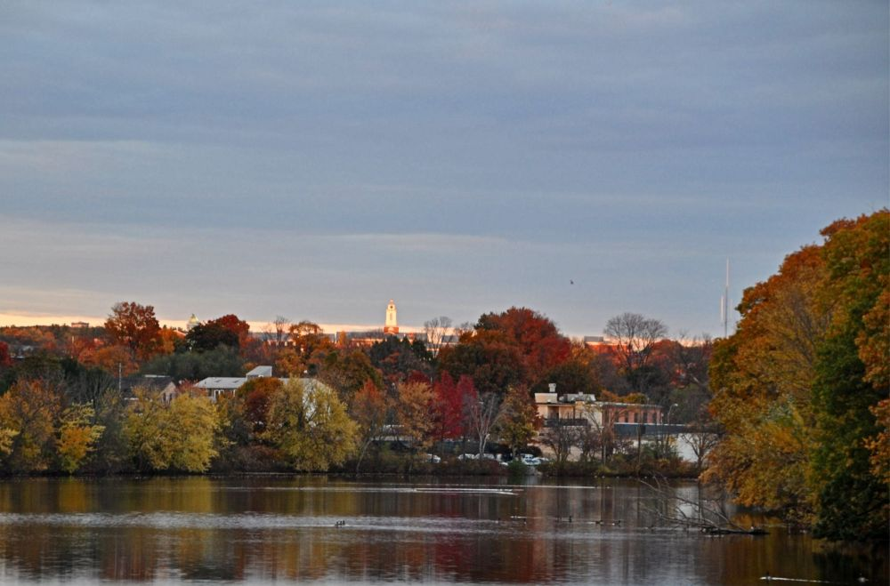 Illuminated white tower at sunset and brilliant foliage reflected in the water. Some scenes are inescapably New England.