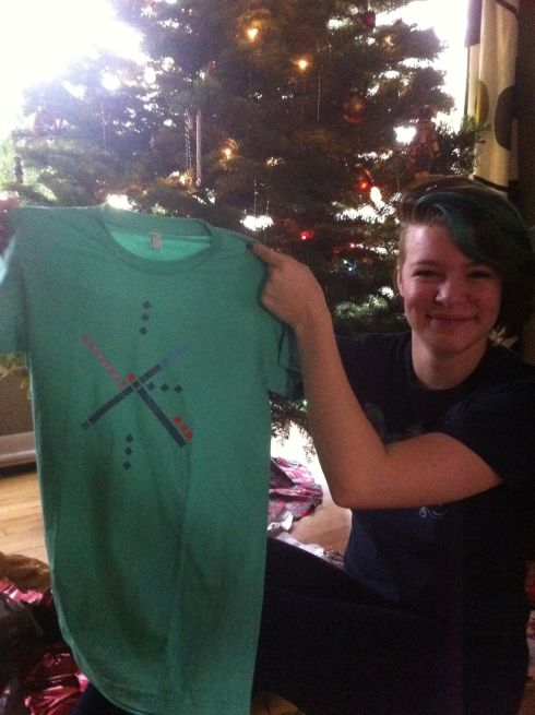 Gift time! Tara's holding a T-shirt with the pattern of the Portland International Airport carpet.