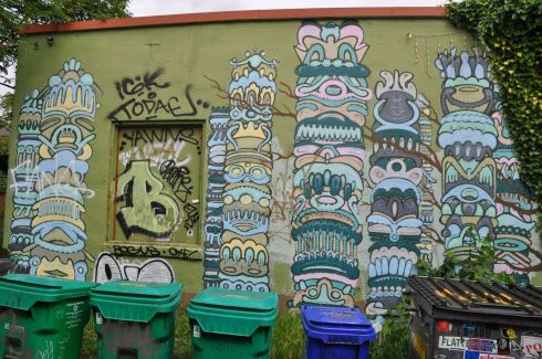 "I get a total charge out of this one. The artwork makes me think of Mayan writing on columns. I can't tell if it was intentional, but each column is stacked ""on top"" of the recycling bins."