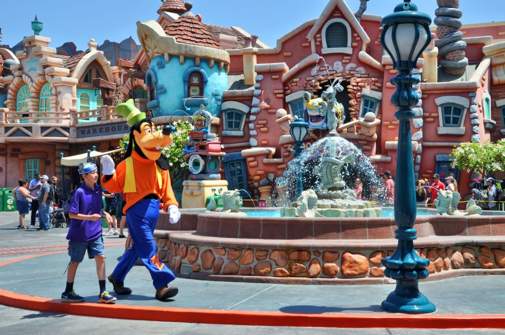 Goofy walks with a fan through Toon Town.