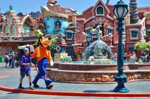 Goofy walks with a fan through Toon Town.