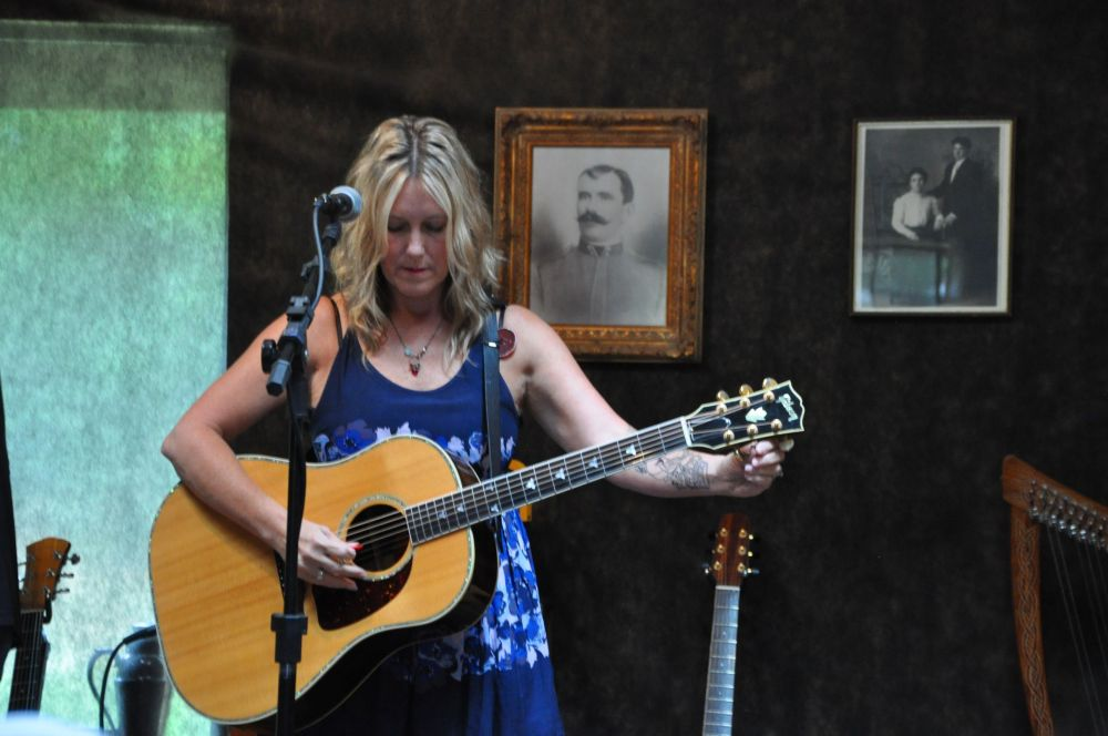 Terry Holder tunes her guitar.