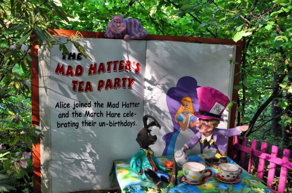 Mad Hatter and March Hare have tea, while the Cheshire Cat looks down, grinning