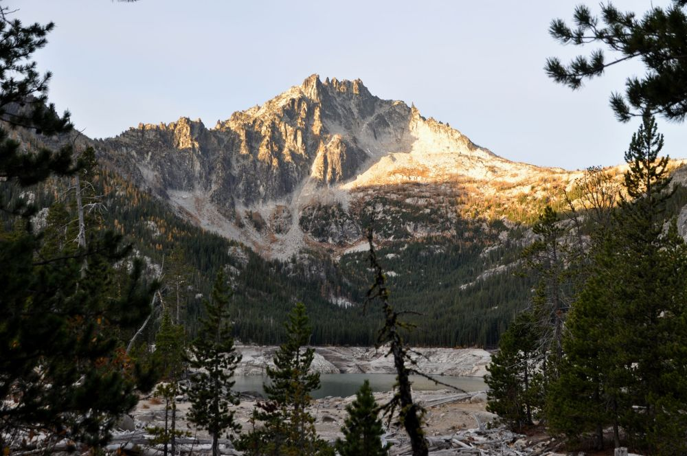 The north side of McClellan Peak lights up in the morning sunshine above Upper Snow Lake.