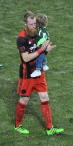 Nat Borchers claps while holding his boy.