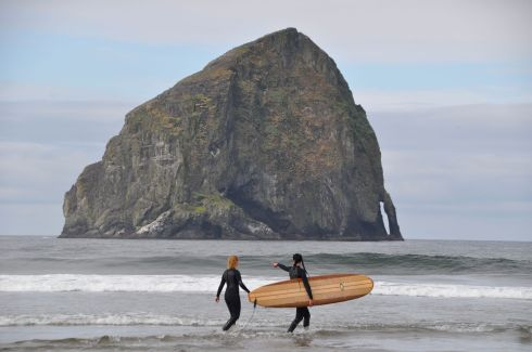 Women head into the water to surf. Pacific City's Haystack Rock sits almost a mile offshore.