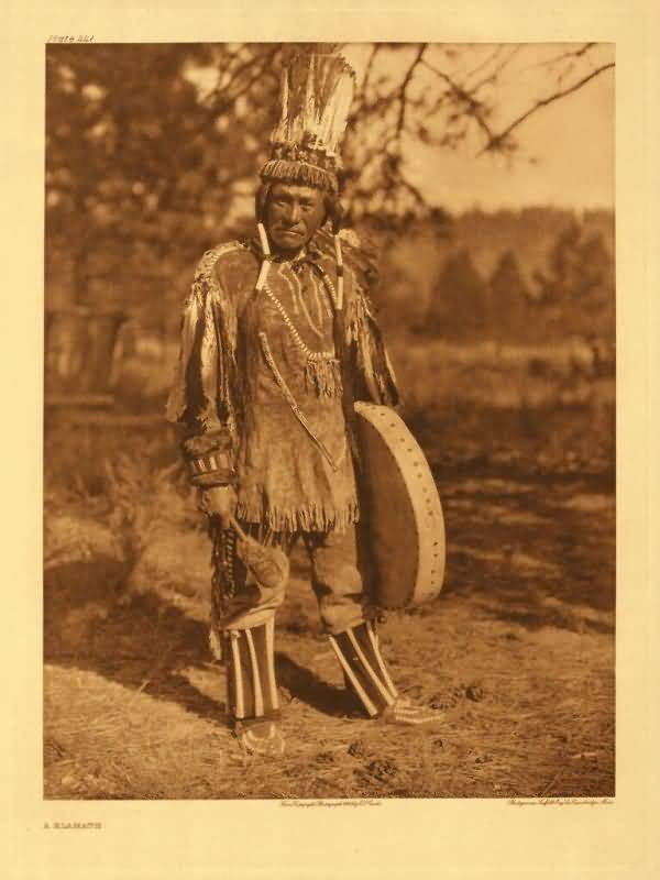 Klamath Indian man stands wearing traditional clothing, wearing a headdress, and holding a drum.